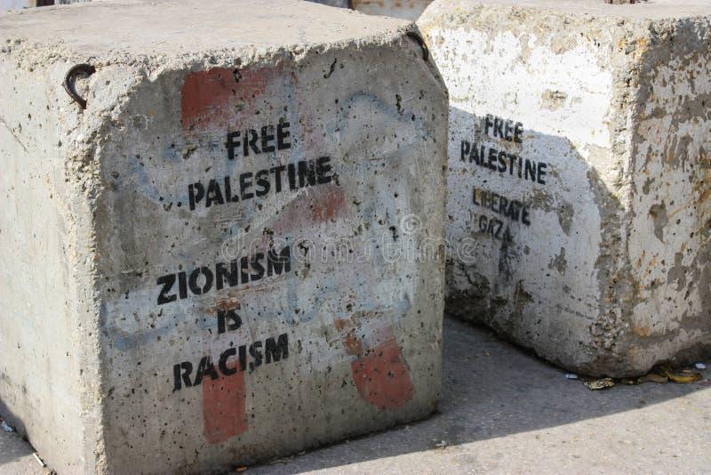 在一条路的封锁在被占领的巴勒斯坦负担一则清楚消息的territory's之间在约旦河西岸或加沙和以色列 库存图片