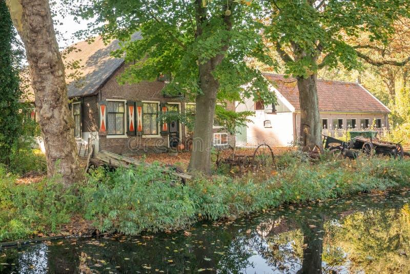 在一条运河在荷兰扁圆形干酪,荷兰附近的风景荷兰老农舍 库存图片