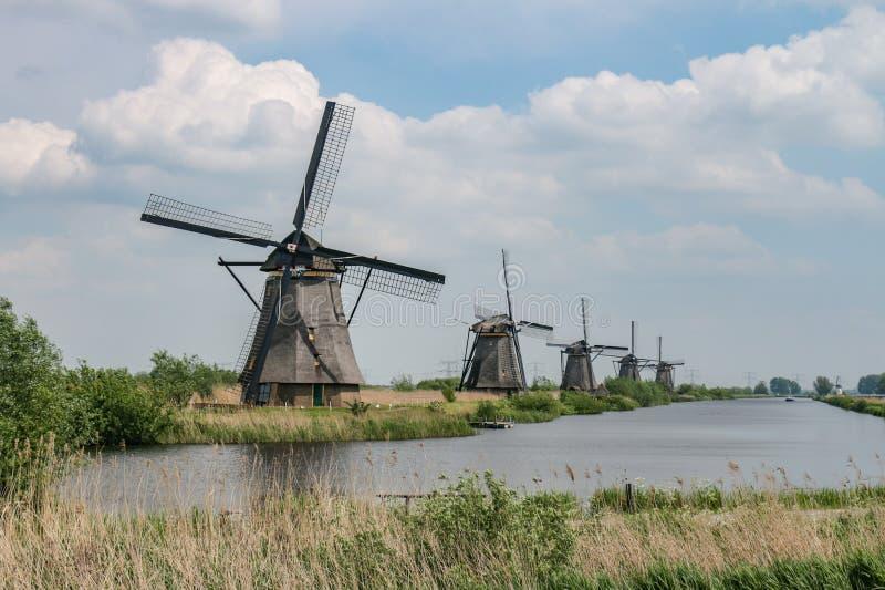 在一条运河的五台历史的荷兰风车在小孩堤防 库存图片