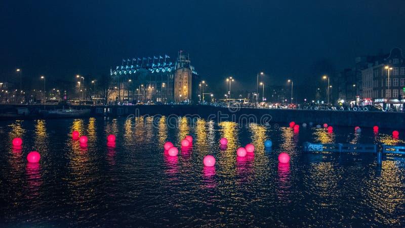 在一条运河的红色色的球在阿姆斯特丹在晚上 免版税图库摄影