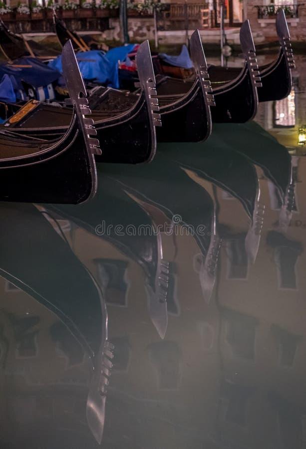 在一条运河的长平底船在威尼斯,显示装饰耶老岛/铁的意大利在小船的弓在水中反射了 库存图片