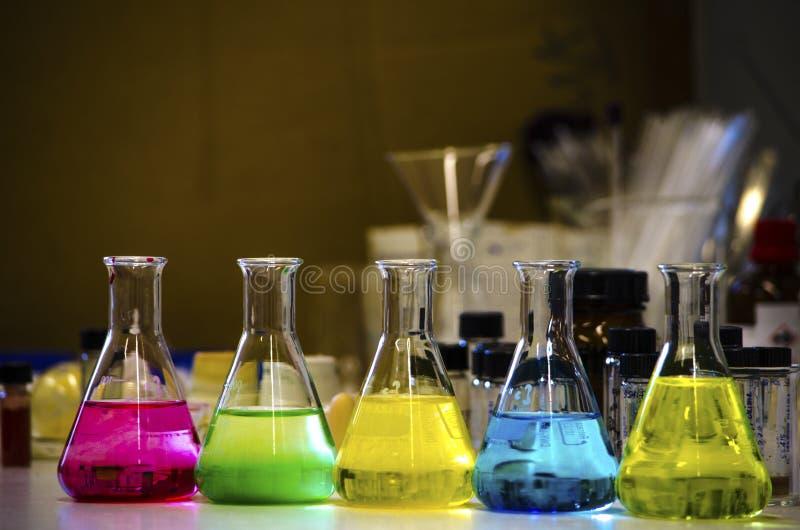 在一条长凳排行的圆锥形烧瓶的五颜六色的解答在有迷离背景有机化学实验的一个化学实验室 免版税库存图片