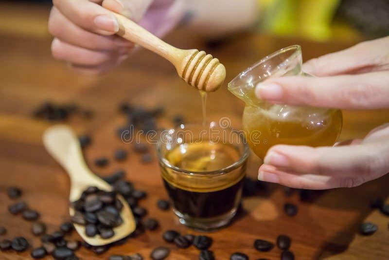 在一杯咖啡的妇女手倾吐的蜂蜜 免版税图库摄影