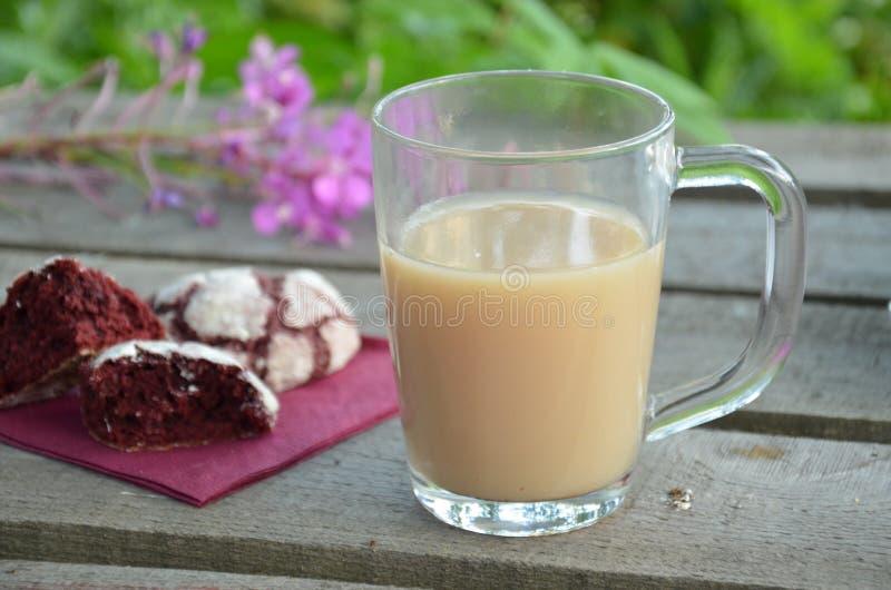 在一杯咖啡的红色天鹅绒曲奇饼旁边 晴朗的春天或夏天早晨 桃红色紫色花 库存照片