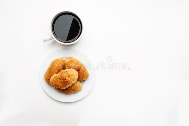 在一杯白色板材和咖啡的新鲜的新月形面包,顶视图,文本空间 免版税图库摄影