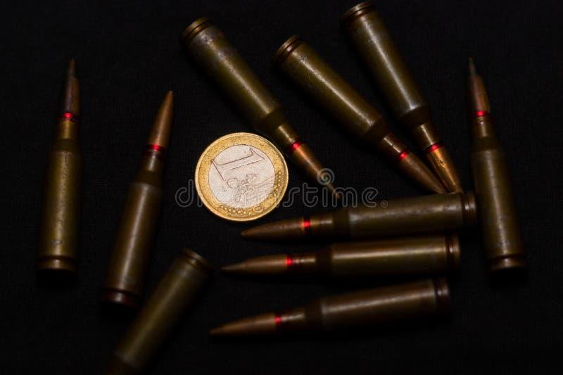 在一枚欧洲硬币附近的步枪弹药在黑背景 象征金钱和其中一个的战争世界` s问题 图库摄影