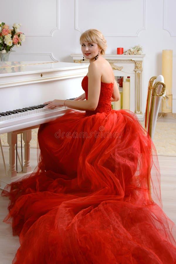 在一架白色大平台钢琴的女性戏剧 免版税图库摄影