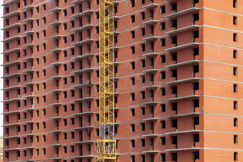 在一栋多层的居民住房的特写镜头建设中从与一台黄色起重机的零件的红砖 ??  免版税库存照片