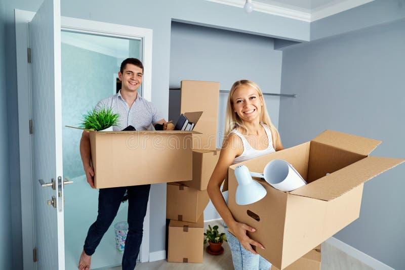 在一栋新的公寓的愉快的夫妇乔迁庆宴的 免版税库存照片