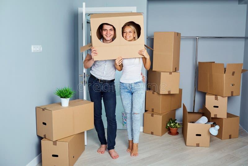 在一栋新的公寓的愉快的快乐的夫妇乔迁庆宴的分开 免版税库存图片