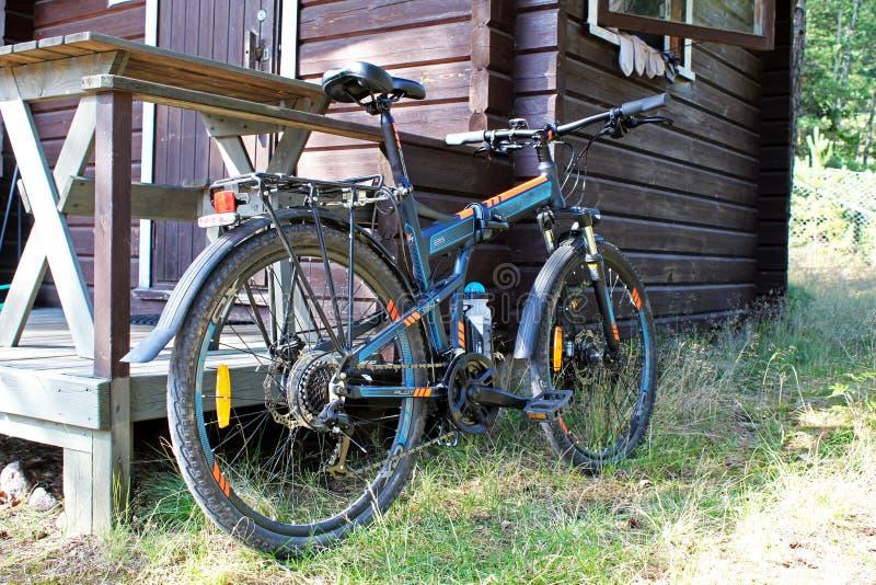 在一栋木乡间别墅附近停放的体育自行车在夏天 免版税库存照片