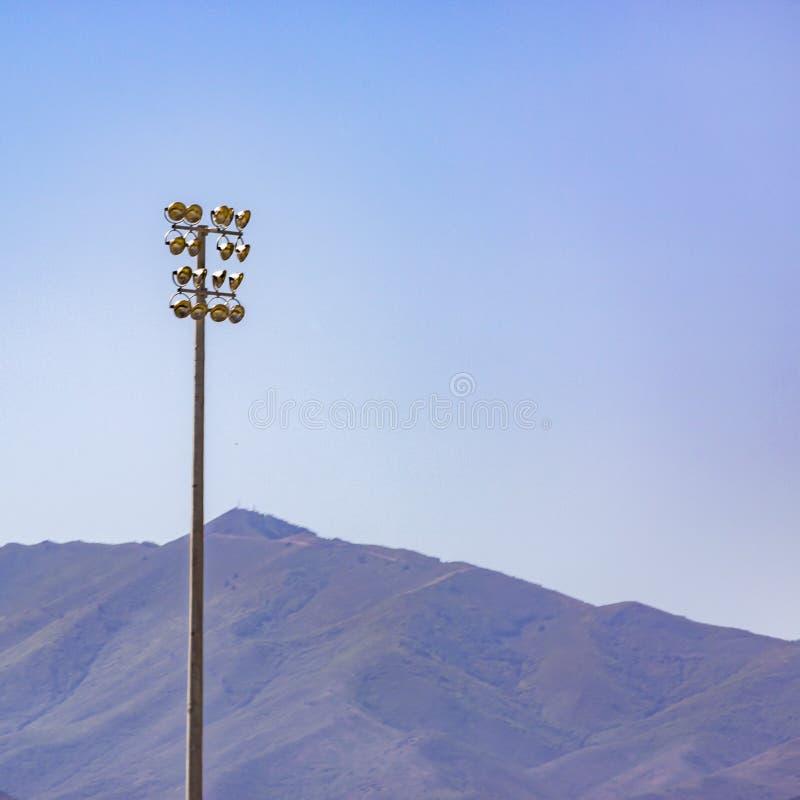 在一根杆的圆的光反对山和天空 库存图片