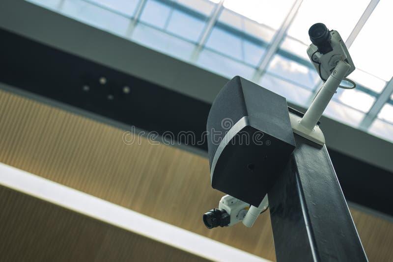 在一根黑柱子的两部白色安全监控相机在机场前提 免版税库存图片
