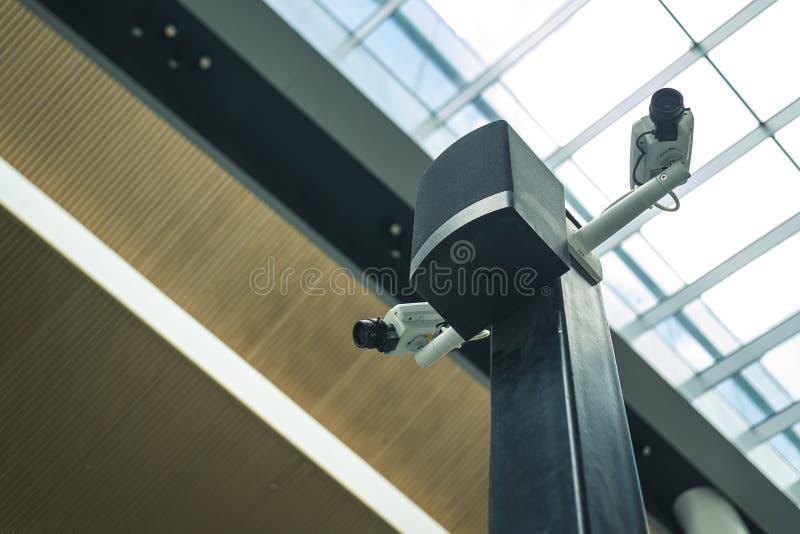 在一根黑柱子的两部白色安全监控相机在机场前提 库存照片