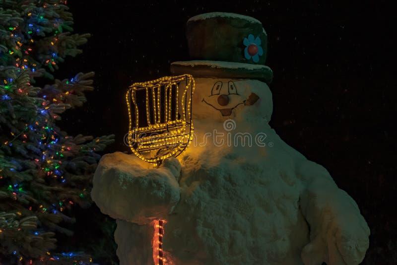 在一棵圣诞树旁边的雪人在晚上 库存照片