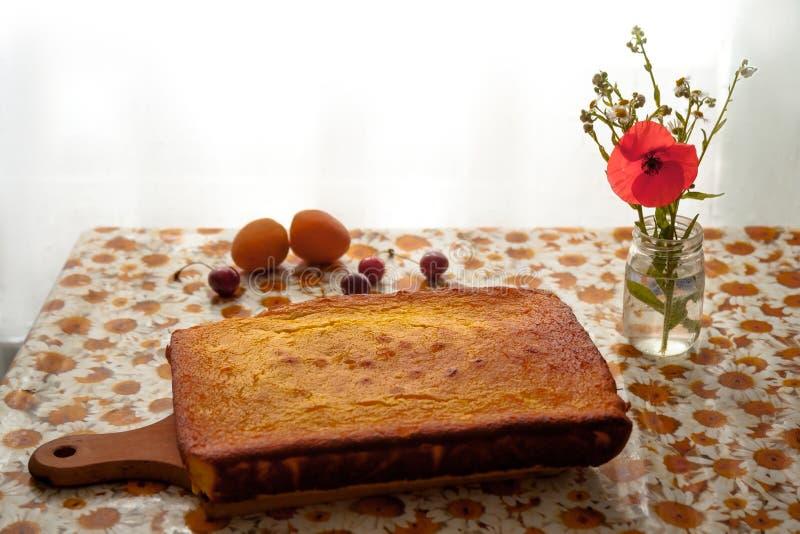 在一棵木切的委员会、鸦片和春黄菊的自创乳酪蛋糕在瓶、杏子和雪利酒在桌上 图库摄影