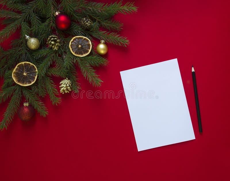 在一棵红色背景绿色云杉分支装饰用圣诞节姜饼、金黄锥体、桔子和球 免版税库存照片