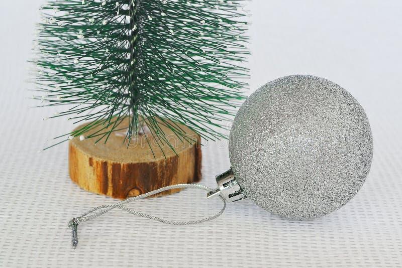 在一棵绿色玩具圣诞树附近的一个发光的银色圣诞节球在白色质地背景,假日概念的结尾 库存图片