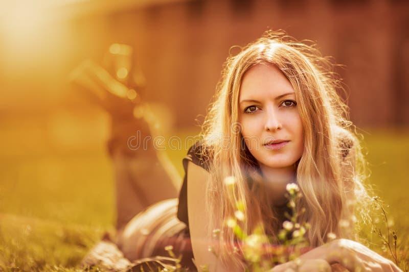 在一棵草的Womanl与花 免版税图库摄影