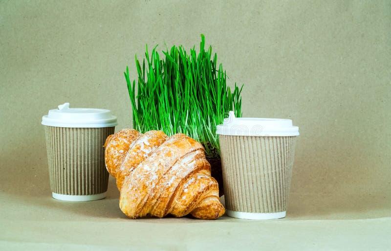 在一次性纸杯和新月形面包的咖啡在绿草背景  有机产品的概念 库存照片