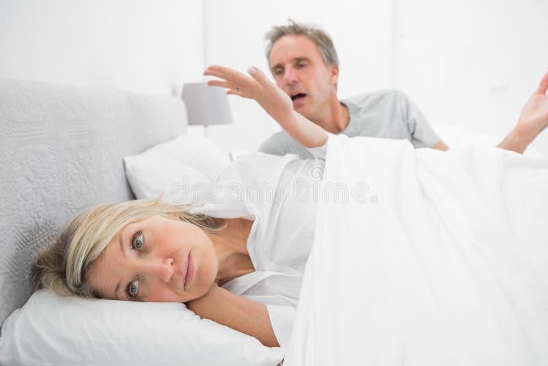 在一次战斗期间在床上,拒绝的妇女听伙伴 免版税库存照片