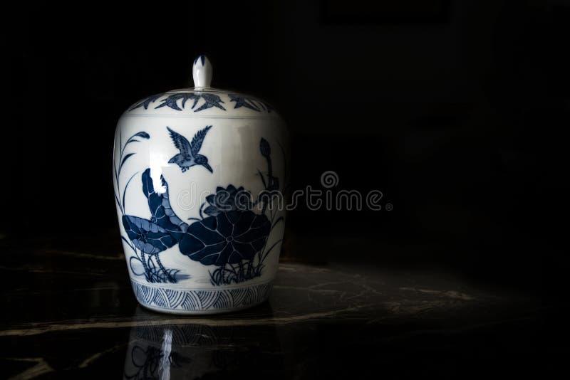 在一次拍卖的古色古香的中国瓷瓶子反对黑背景 空的拷贝空间 免版税库存照片