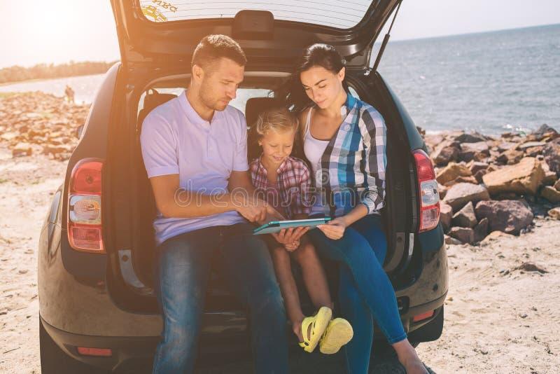 在一次旅行的愉快的家庭在他们的汽车 爸爸、妈妈和女儿由海旅行或海洋或者河 免版税库存照片