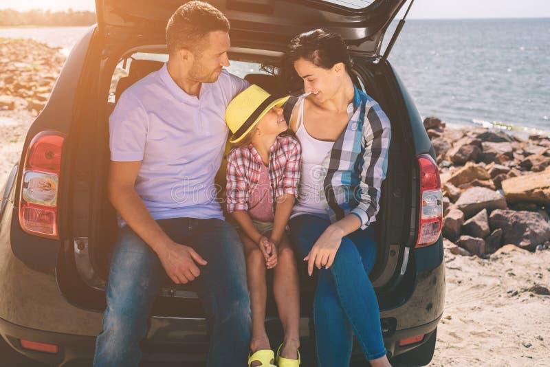 在一次旅行的愉快的家庭在他们的汽车 爸爸、妈妈和女儿由海旅行或海洋或者河 库存照片
