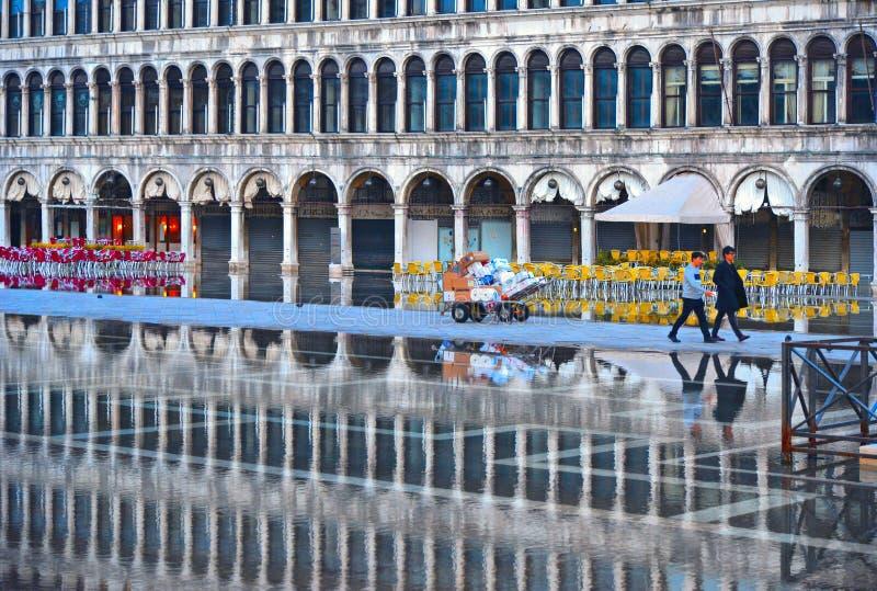 在一次洪水期间的威尼斯,意大利空的圣马克的广场与历史大厦的美好的水反射在湿f的 免版税库存图片