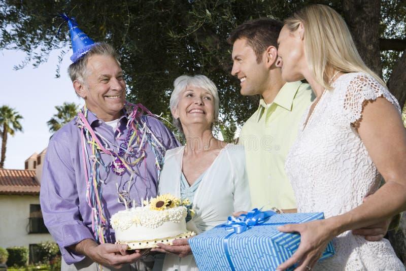 在一次生日聚会期间的两对夫妇在庭院里 免版税库存图片