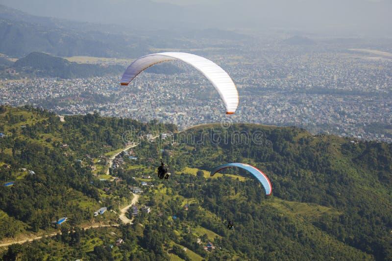 在一次白色和蓝色降伞飞行的两个滑翔伞在绿色山谷的一个城市 免版税库存图片