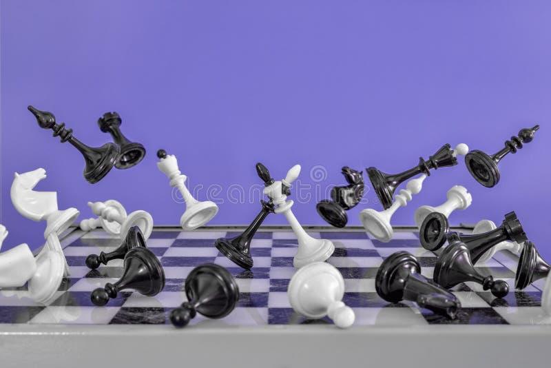 在一次紫色背景飞行的棋子远离中心 争斗国王在中部 库存照片