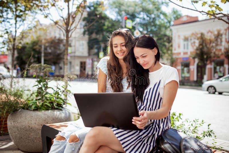 在一温和的日子,两个年轻亭亭玉立的深色头发的朋友,佩带,casul样式,下来坐长凳并且寻找信息  免版税图库摄影