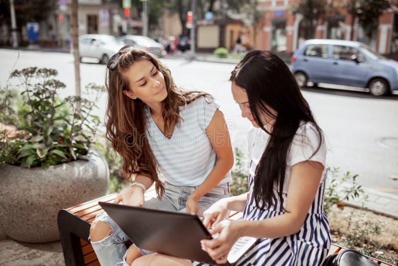 在一温和的日子,有长的黑发的,佩带的便装样式两美女,坐下了在一分钟并且打开了膝上型计算机 图库摄影