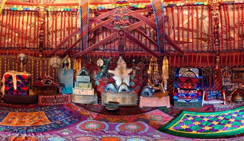 在一游牧yurt内部的传统地毯、地毯和枕头治疗细节 库存图片