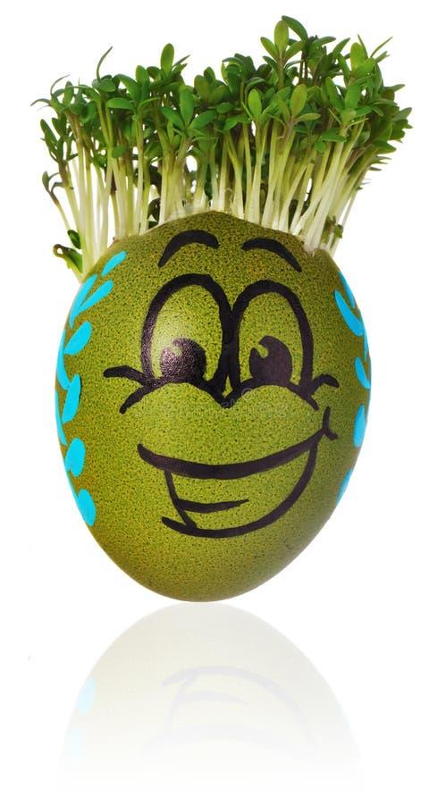在一滑稽的兴高采烈的人面孔和colo绘的手工制造复活节彩蛋 免版税图库摄影