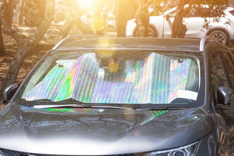 在一热的天停放的客车的挡风玻璃的下防护反射性表面,加热被在里面的太阳的光芒 免版税图库摄影