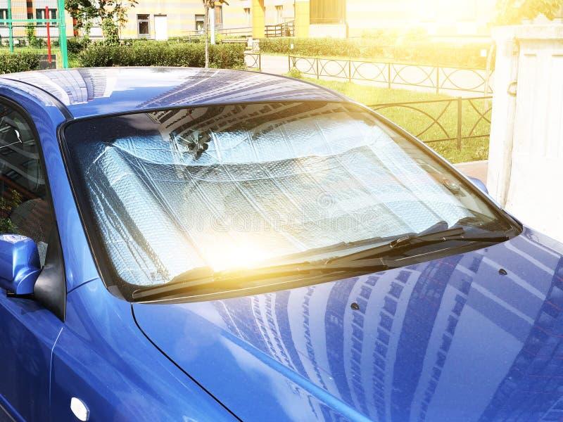 在一热的天停放的客车的挡风玻璃的下防护反射性表面,加热被在里面的太阳的光芒 免版税库存图片