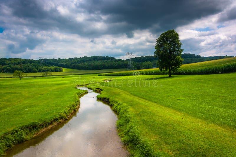 在一片农田的小小河在农村卡洛尔县,马里兰 免版税库存照片