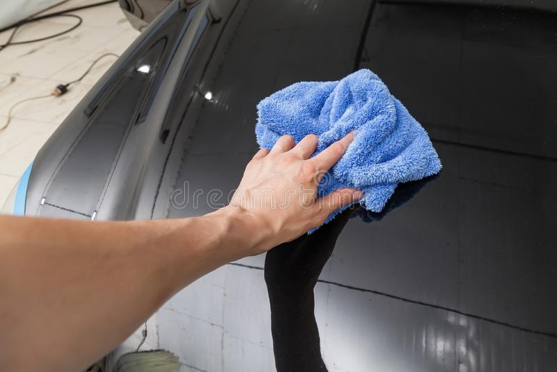 在一男性擦净剂的手上的特写镜头与在洗涤和申请防护以后抹一辆黑汽车的一块蓝色microfiber布料的 库存照片