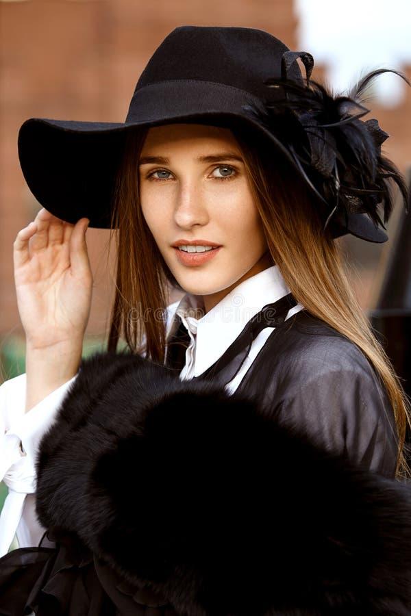 在一白色衬衫、黑色裤子和一个帽子的一件黑时髦的夹克打扮的时兴的亭亭玉立的长发女孩有宽的 免版税库存图片
