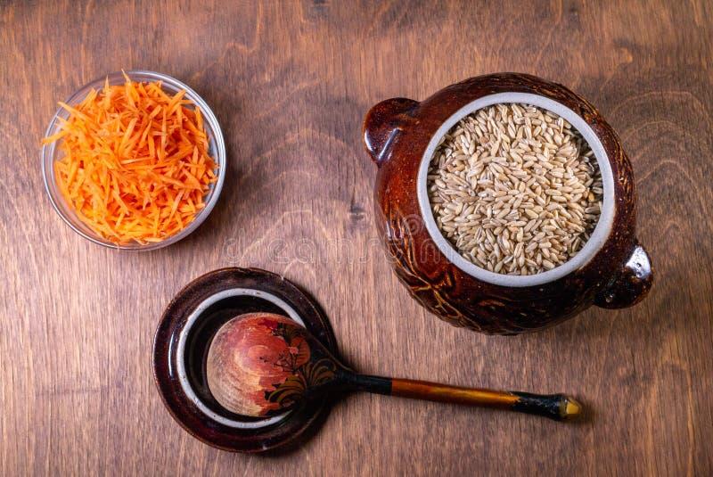 在一碗燕麦粥,有一把木匙子在它旁边,在碗的一棵切的红萝卜 库存照片