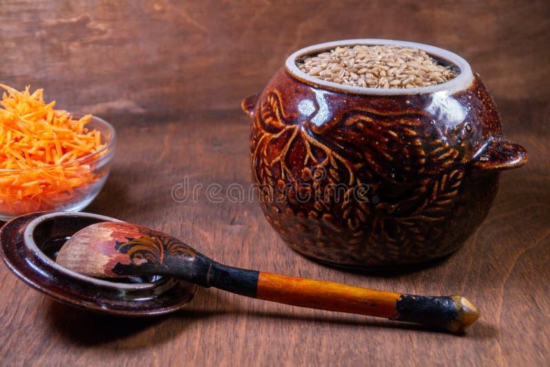 在一碗燕麦粥,有一把木匙子在它旁边,在碗的一棵切的红萝卜 免版税库存照片