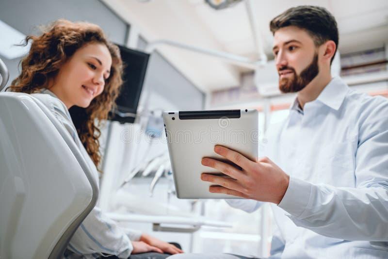 在一种片剂应用的愉快的牙医和患者评论的治疗在咨询用医疗设备在背景中 库存图片