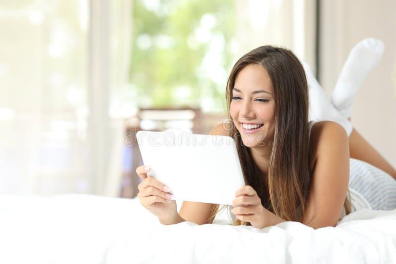 在一种片剂的女孩观看的录影在床上 免版税库存图片