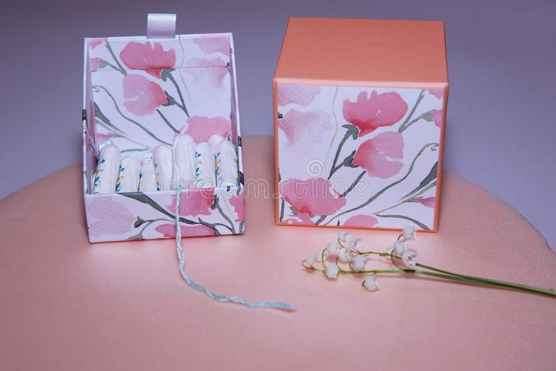 在一箱的干净的白色棉花棉塞在桃红色背景的棉塞 ?? 女性卫生学在期间,治疗 免版税库存图片