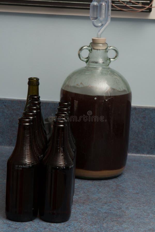 在一篮装的细类颈大坛有气密室的和黑暗的瓶的被发酵的啤酒在厨房里 免版税图库摄影