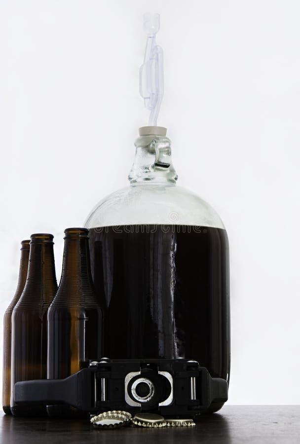 在一篮装的细类颈大坛的被发酵的啤酒有有黑褐色瓶和盖帽的气密室和手封盖罐头的人的 免版税库存照片