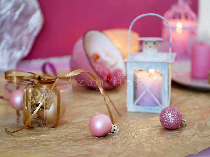 在一粉色的装饰构成从灼烧的蜡烛,装饰灯笼,在盘,圣诞节装饰,球的东方甜点 库存照片