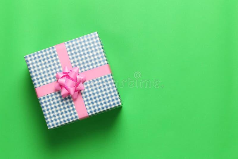 在一绿色加工印刷纸地板和ha安置的蓝色圣诞礼物箱子 图库摄影